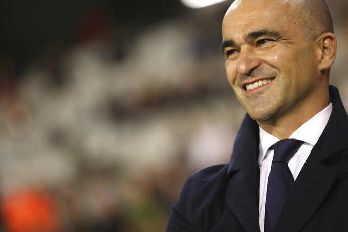 FILE - In this photo taken on Thursday, Oct. 10, 2019, Belgium's coach Roberto Martinez smiles prior to the Euro 2020 group I qualifying soccer match between Belgium and San Marino at the King Baudouin Stadium in Brussels. Martinez has signed a new contract to lead the Red Devils through the 2022 World Cup in Qatar. (AP Photo/Francisco Seco)