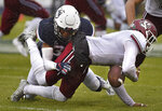 Connecticut defensive back Ryan Carroll, left, takes down Massachusetts wide receiver Brennon Dingle during the first half of an NCAA college football game, Saturday, Oct. 27, 2018, in East Hartford, Conn. (AP Photo/Jessica Hill)