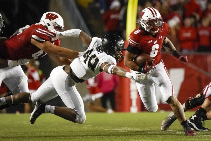 Wisconsin's Chez Mellusi runs past Army's Jaylen Jacobs during the second half of an NCAA college football game Saturday, Oct. 16, 2021, in Madison, Wis. (AP Photo/Morry Gash)