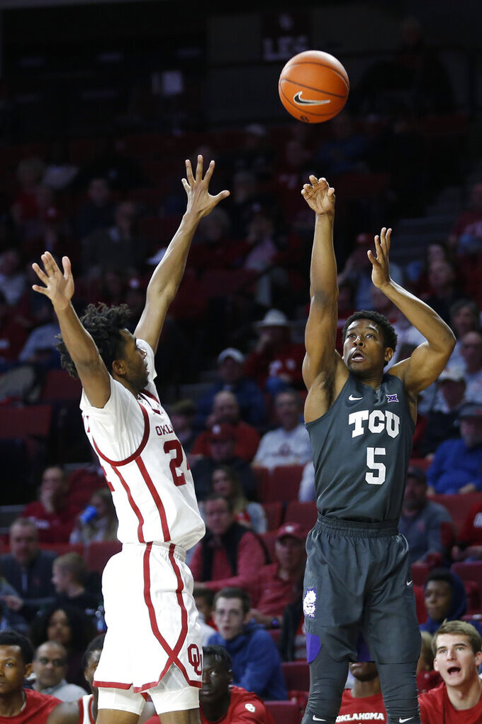 TCU's Jaire Grayer (5) takes a shot over Oklahoma's Jamal Bieniemy (24) during the first half of an NCAA college basketball game in Norman, Okla., Saturday, Jan. 18, 2020. (AP Photo/Garett Fisbeck)