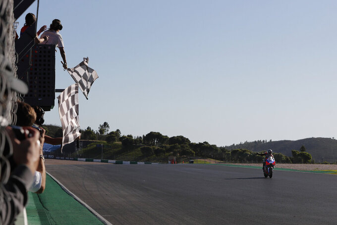 MotoGP rider Miguel Oliveira of Portugal celebrates as he crosses the finish line to win the MotoGP race of the Portuguese Motorcycle Grand Prix, the last race of the season, at the Algarve International circuit near Portimao, Portugal, Sunday, Nov. 22, 2020. (AP Photo/Armando Franca)