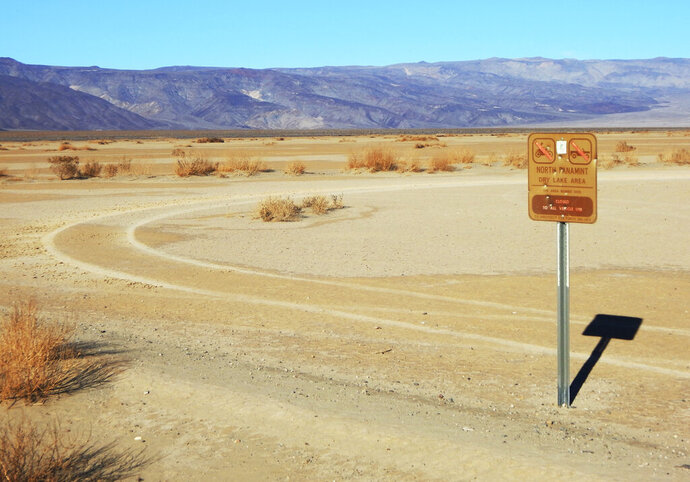This undated photo provided by the U.S. National Park Service shows vehicle tracks beyond a sign banning vehicles in the North Panamint dry lake area during the recent federal government shutdown in an area of Death Valley National Park, Calif. National parks across the United States are scrambling to clean up and repair damage caused by visitors and storms during the government shutdown while bracing for another possible closure ahead of the usually busy President's Day weekend. (National Park Service via AP)