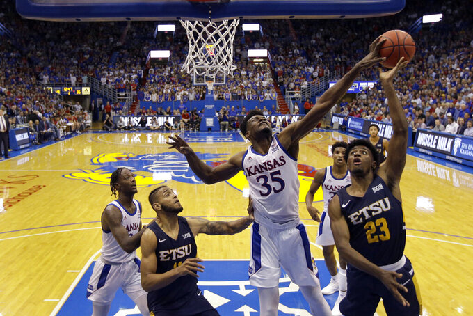 Kansas center Udoka Azubuike (35) blocks a shot by East Tennessee State forward Vonnie Patterson (23) during the second half of an NCAA college basketball game Tuesday, Nov. 19, 2019, in Lawrence, Kan. Kansas won 75-63. (AP Photo/Charlie Riedel)