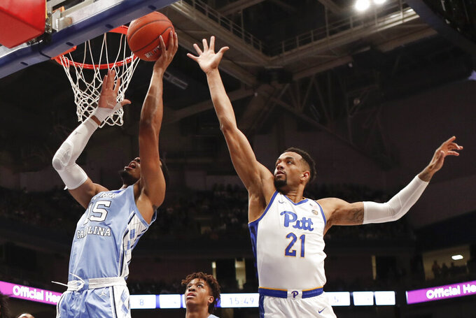 North Carolina's Garrison Brooks (15) shoots as Pittsburgh's Terrell Brown (21) defends during the first half of an NCAA college basketball game, Saturday, Jan. 18, 2020, in Pittsburgh. (AP Photo/Keith Srakocic)