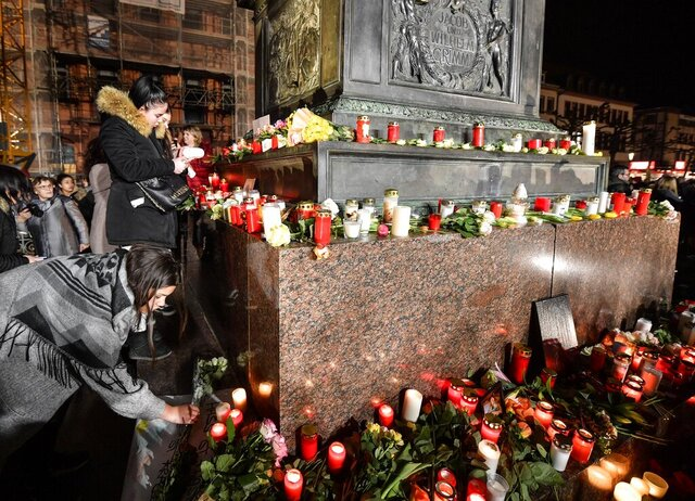 People place candles and flowers at a monument on the market place during a mourning for the victims of the shooting in Hanau, Germany, Thursday, Feb. 20, 2020. A 43-year-old German man shot and killed nine people at several locations in a Frankfurt suburb overnight in attacks that appear to have been motivated by far-right beliefs, officials said Thursday. (AP Photo/Martin Meissner)