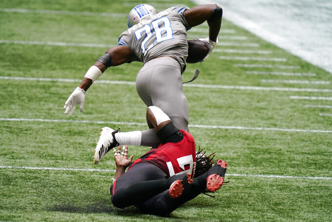Atlanta Falcons defensive end Takkarist McKinley (98) trips up Detroit Lions running back Adrian Peterson (28) during the first half of an NFL football game, Sunday, Oct. 25, 2020, in Atlanta. (AP Photo/Brynn Anderson)