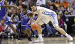 Duke's Zion Williamson, left, and North Carolina's Luke Maye, right, chase a loose ball during the first half of an NCAA college basketball game in the Atlantic Coast Conference tournament in Charlotte, N.C., Friday, March 15, 2019. (AP Photo/Chuck Burton)