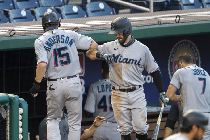 Miami Marlins' Brian Anderson (15) is congratulated by teammate Jon Berti (5) after scoring on Jonathan Villar's single during the fourth inning of a baseball game against the Washington Nationals in Washington, Monday, Aug. 24, 2020. (AP Photo/Manuel Balce Ceneta)