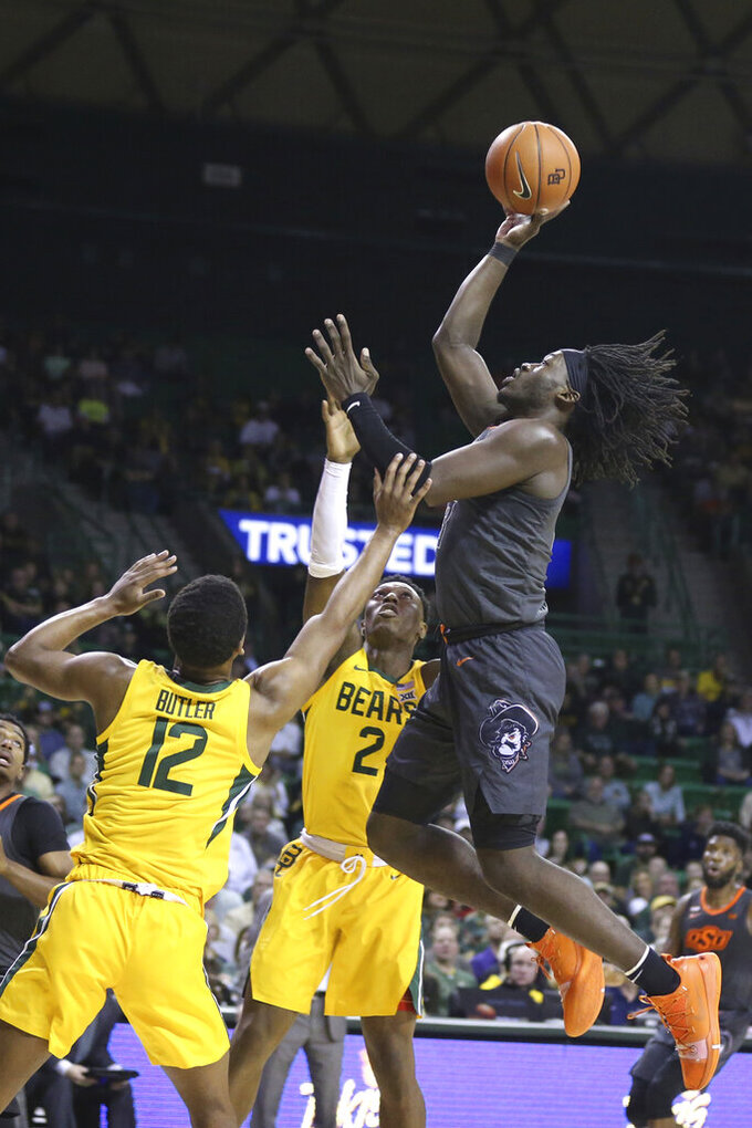 Oklahoma State guard Isaac Likekele, right, shoots over Baylor guard Jared Butler (12) during the first half of an NCAA college basketball game Saturday, Feb. 8, 2020, in Waco, Texas. (AP Photo/Rod Aydelotte)