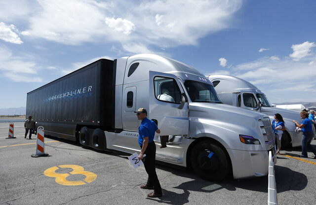 FILE - In this May 6, 2015 file photo people load in to a Daimler Freightliner Inspiration self-driving truck for a demonstration in Las Vegas. Daimler Trucks and allied vehicle software company Torc Robotics announced Thursday, Sept. 3, 2020, the expansion of testing for self-driving trucks to public roads in New Mexico along major long-haul freight routes. (AP Photo/John Locher,File)