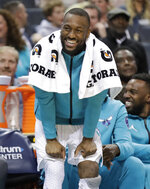 "FILE - In this March 26, 2019, file photo, Charlotte Hornets' Kemba Walker laughs at a play from the bench during the first half of an NBA basketball game against the San Antonio Spurs in Charlotte, N.C.  The three-time All-Star point says he'd be willing to work with the Hornets and take less than the ""supermax"" $221 million contract he's eligible to receive to re-sign with Charlotte. (AP Photo/Chuck Burton, File)"
