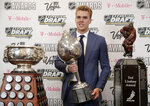 FILE - In this Wednesday, June 21, 2017 file photo, Connor McDavid of the Edmonton Oilers poses with the Art Ross Trophy, left, the Hart Memorial Trophy, center, and the Ted Lindsay Award after winning the honors during the NHL Awards in Las Vegas. Connor McDavid is the first player to shake off personal stats, awards and achievements and put the focus on his team in Edmonton. Yet there he is on the cover of a video game or in a commercial for a bank. (AP Photo/John Locher, File)