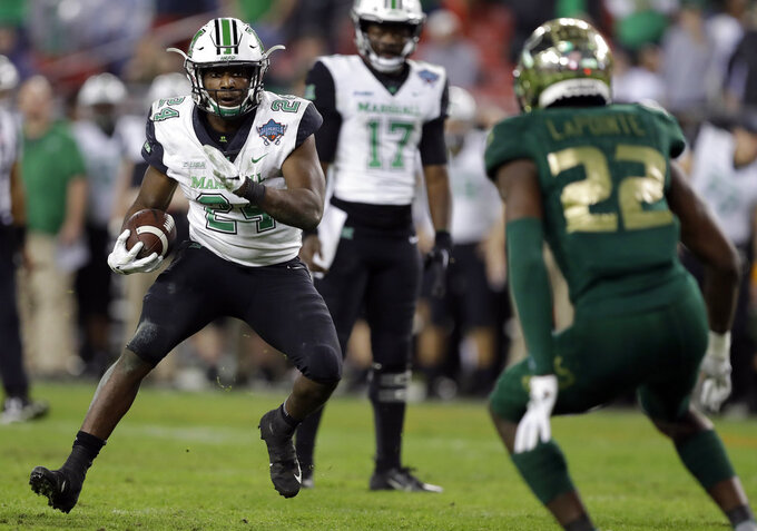 Marshall running back Keion Davis (24) carries as South Florida defensive back Mekhi LaPointe (22) watches during the second half of the Gasparilla Bowl NCAA college football game Thursday, Dec. 20, 2018, in Tampa, Fla. (AP Photo/Chris O'Meara)