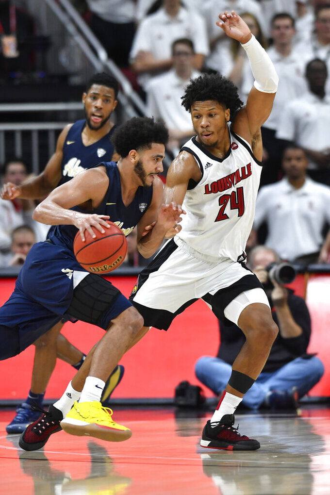 Akron guard Tyler Cheese (4) attempts to drive past the defense of Louisville forward Dwayne Sutton (24) during the second half of an NCAA college basketball game in Louisville, Ky., Sunday, Nov. 24, 2019. (AP Photo/Timothy D. Easley)
