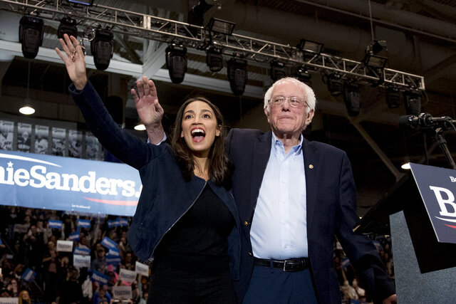 """FILE - In this Feb. 10, 2020 file photo, Democratic presidential candidate Sen. Bernie Sanders, I-Vt., accompanied by Rep. Alexandria Ocasio-Cortez, D-N.Y., left, takes the stage at campaign stop at the Whittemore Center Arena at the University of New Hampshire in Durham, N.H. Choosing a presidential candidate based primarily on loathing the alternative is not the strongest of electoral strategies. That's why leaders of the progressive movement say many Americans who were enthralled by Bernie Sanders and his slogan of """"Not Me. Us,"""" won't be as likely to settle for Joe Biden.  (AP Photo/Andrew Harnik)"""