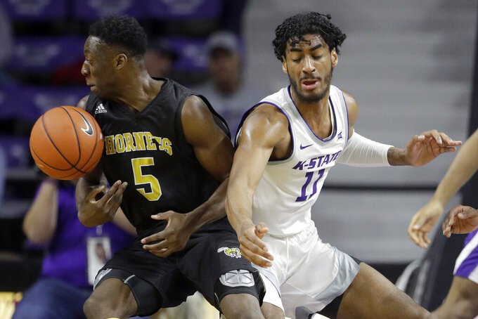 Kansas State's Antonio Gordon (11) knocks the ball away from Alabama State's Tobi Ewuosho (5) during the first half of an NCAA college basketball game Wednesday, Dec. 11, 2019, in Manhattan, Kan. (AP Photo/Charlie Riedel)