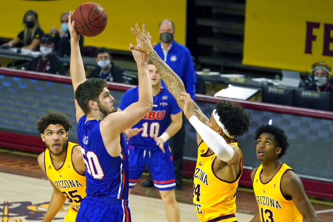 Houston Baptist center Ryan Gomes (50) shoots over Arizona State forward Jalen Graham (24), Josh Christopher (13), and Taeshon Cherry (35) during the second half of an NCAA college basketball game, Sunday, Nov. 29, 2020, in Tempe, Ariz. (AP Photo/Rick Scuteri)