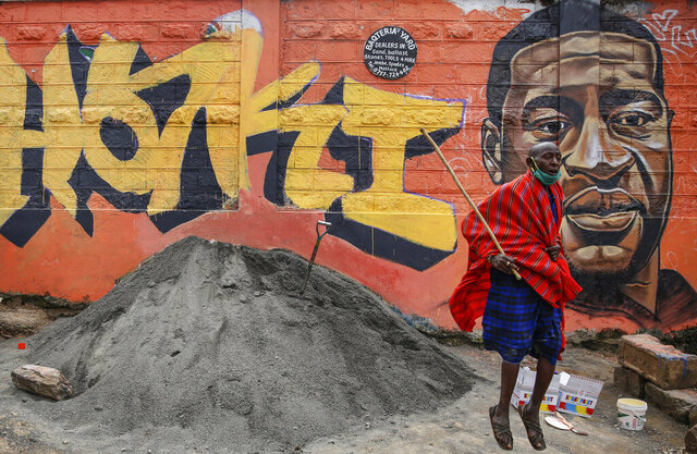 FILE - In this Wednesday, June 3, 2020 file photo a Maasai man, who said he had seen videos on Facebook about protests in the U.S. over the death of George Floyd, jumps next to a new mural painted this week showing Floyd with the Swahili word