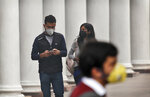 Indians walk wearing pollution masks in New Delhi, India, Thursday, Nov. 14, 2019. Schools in India's capital have been shut for Thursday and Friday after air quality plunged to a severe category for the third consecutive day, enveloping New Delhi in a thick gray haze of noxious air. (AP Photo/Manish Swarup)