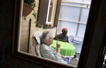 In this photo taken on Monday, June 22, 2020, Eric Baranyanka, right, speaks with his foster mother Emma Monsaert in Lembeek, Belgium. Baranyanka fled political persecution in the Belgian protectorate of Burundi in the 1960's, landing half a world away at a military airport in Brussels, before being fostered by Emma Monsaert and her husband Paul. (AP Photo/Virginia Mayo)