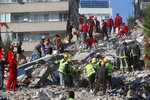 Members of rescue services search for survivors in the debris of a collapsed building in Izmir, Turkey, Saturday, Oct. 31, 2020. Rescue teams on Saturday ploughed through concrete blocs and debris of eight collapsed buildings in Turkey's third largest city in search of survivors of a powerful earthquake that struck Turkey's Aegean coast and north of the Greek island of Samos, killing dozens Hundreds of others were injured. (AP Photo/Darko Bandic)