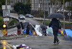 FILE - In this Jan. 17, 2019, file photo, pedestrians make their way along a rain soaked Hollywood Blvd., in Los Angeles. Mayor Eric Garcetti is paying a political price for the city's homeless crisis. An effort is underway to recall the two-term Democrat from office prompted by widespread complaints about homeless encampments throughout the city. Figures released earlier this month showed a 16% jump in LA's homeless population over the last year, pegging it at 36,300, the size of a small city. (AP Photo/Richard Vogel, File)