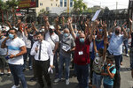FILE - This Wednesday, July 29, 2020 file photo, dozens of Palestinians flash the victory sign as they protest against their permanent settlement in Lebanon and demanding immigration, near the U.S. embassy in Aukar, northeast of Beirut, Lebanon.  The financial crisis that the U.N. agency for Palestinian refugees is experiencing could lead to ceasing some of its activities in what would raise risks of instability in this volatile region, the head of the agency said Wednesday, Sept. 16.  (AP Photo/Bilal Hussein, File)