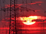 FILE-In this June 5, 2019 file photo the sun rises behind power poles near Frankfurt, Germany. Researchers calculate that the electricity required for the virtual currency bitcoin generates as much carbon dioxide as cities like Las Vegas or Hamburg. (AP Photo/Michael Probst)