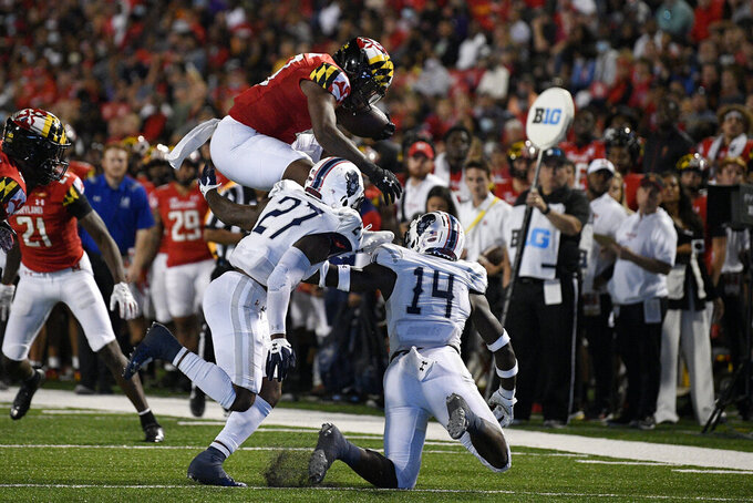 Maryland running back Peny Boone, top, leaps for yardage against Howard defensive backs Kenny Gallop (14) and Aaron Walker (27) during the first half of an NCAA college football game, Saturday, Sept. 11, 2021, in College Park, Md. (AP Photo/Nick Wass)