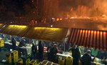 In this image made from video on Saturday, March 16, 2019, local people rest at concessions stands as a bonfire burns in the background, in Lustenau, Austria. An Austrian town has burned what organizers says is the world's tallest bonfire, clocking in at 60.646 meters (198.97 feet). The local bonfire group in Lustenau, near the Swiss border, took three months to build the structure. The previous record structure was a 47-meter (154.2-foot) bonfire in Alesund, Norway in 2016. (AP Photo)