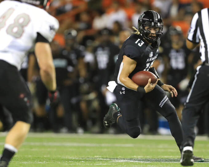 Hawaii quarterback Cole McDonald (13) scrambles through the UNLV defense trying to gain yards during the second quarter of an NCAA college football game, Saturday, Nov. 17, 2018, in Honolulu. (AP Photo/Marco Garcia)