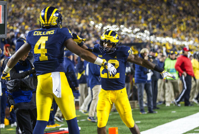 Michigan wide receiver Nico Collins (4) celebrates his 2-point conversion with running back Karan Higdon (22) during the third quarter of an NCAA college football game against Wisconsin in Ann Arbor, Mich., Saturday, Oct. 13, 2018. Michigan won 38-13. (AP Photo/Tony Ding)