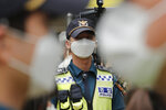 Police officers wearing face masks to help protect against the spread of the new coronavirus stand guard near the Japanese embassy in Seoul, South Korea, Wednesday, July 1, 2020. (AP Photo/Ahn Young-joon)