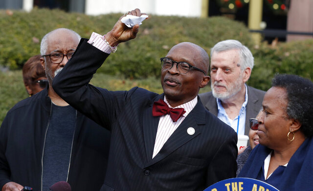 The Rev. T. Anthony Spearman, president of the NC NAACP, crumples up a mailer that tells voters IDs are needed in the upcoming 2020 election during a press conference outside the Legislative Building in Raleigh, N.C., Friday, Dec. 27, 2019. The press conference was held after a federal judge in North Carolina said Thursday she would block the NC voter ID law, at least temporarily, as a lawsuit against the state continues. (Ethan Hyman/The News & Observer via AP)