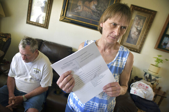 Carol Dworshak holds the official document citing foreclosure of their modest home in Mandan, N.D. on June 5, 2019.