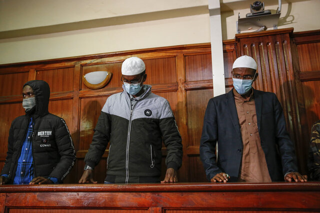 Hussein Hassan Mustafah, left, and Mohamed Ahmed Abdi, right, who were both found guilty of supporting the gunmen involved in the Westgate Mall attack in Sept. 2013, stand with Liban Abdullah Omar, center, who was found innocent, as the verdict is delivered in their trial at Milimani court in the capital Nairobi, Kenya Wednesday, Oct. 7, 2020. A Kenyan court on Wednesday found two men guilty of supporting the 2013 attack by gunmen with the Somalia-based extremist group al-Shabab on Nairobi's upscale Westgate Mall that left 67 people dead, while Chief Magistrate Francis Andayi acquitted a third suspect. (AP Photo/Brian Inganga)