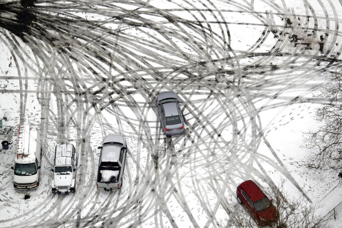FILE - In this Feb. 11, 2019, file photo a car maneuvers through a still snow-covered parking lot in Seattle. With the eastern two-thirds of the U.S. shivering through an early blast of arctic air, it's time to start thinking about whether your car's tires will get you safely through the winter. (AP Photo/Elaine Thompson, File)