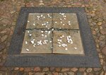 "In this Tuesday, Jan. 14, 2020 photo stones are dropped at a commemorative plaque besides the Stadtkirche (Town Church) in Wittenberg, Germany. The church contains a so-called ""Judensau,"" or ""Jew pig,"" sculpture which is located about 4 meters, 13 feet, above the ground on a corner of the church. A court in eastern Germany will consider next week a Jewish man's bid to force the removal of an ugly remnant of centuries of anti-Semitism from a church where Martin Luther once preached. (AP Photo/Jens Meyer)"
