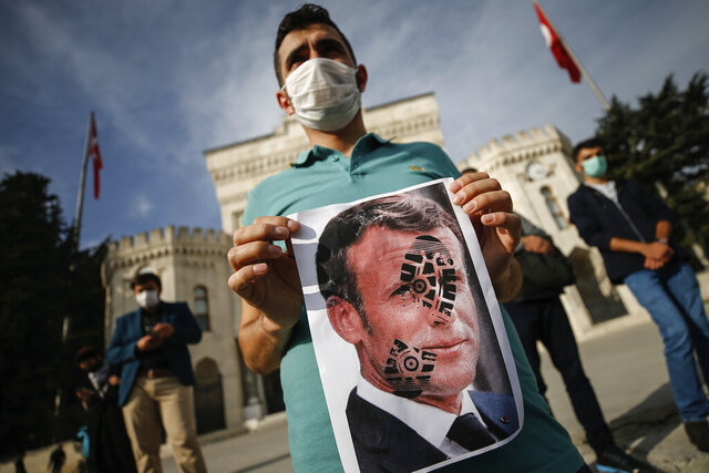 A youth holds a photograph of France's President Emmanuel Macron, stamped with a shoe mark, during a protest against France in Istanbul, Sunday, Oct. 25, 2020. Turkish President Recep Tayyip Erdogan on Sunday challenged the United States to impose sanctions against his country while also launching a second attack on French President Emmanuel Macron. Speaking a day after he suggested Macron needed mental health treatment because of his attitude to Islam and Muslims, which prompted France to recall its ambassador to Ankara, Erdogan took aim at foreign critics. (AP Photo/Emrah Gurel)