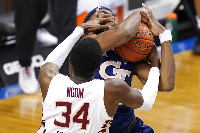 Florida State center Tanor Ngom (34) fouls Georgia Tech forward Moses Wright (5) during the second half of an NCAA college basketball Championship game of the Atlantic Coast Conference tournament in Greensboro, N.C., Saturday, March 13, 2021. (AP Photo/Gerry Broome)