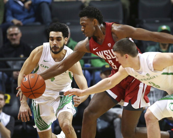 Washington State Oregon's Ehab Amin, left, and Payton Pritchard battle Washington State's Robert Franks Jr. for a loose ball during the first half of an NCAA college basketball game Sunday, Jan 27, 2019, in Eugene, Ore. (AP Photo/Chris Pietsch)