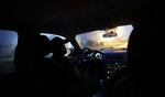 In this Thursday, March 14, 2019, photo, Border Patrol agent Hermann Rivera drives in McAllen, Texas, near the U.S.-Mexico border on a patrol searching for immigrants who have entered the country illegally. The agency says apprehensions along the border have surged, particularly of migrant parents and children from Central America. (AP Photo/Eric Gay)