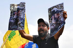A Hezbollah supporter chant slogans and hold posters of the late Hezbollah military commander Imad Mughniyeh, while protesting the visit to Lebanon by Gen. Frank McKenzie, the head of U.S. Central Command, outside ​​the Rafik Hariri International Airport in Beirut, Lebanon, Wednesday, July 8, 2020. (AP Photo/Bilal Hussein)