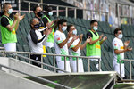 FILE-In this May 31, 2020 file photo Moenchengladbach alternate players wearing face masks applaud during the German Bundesliga soccer match between Borussia Moenchengladbach and Union Berlin in Moenchengladbach, Germany. Bundesliga clubs are sounding the alarm over players returning from international duty with the coronavirus as Germany's daily infection rate continues to rise. (AP Photo/Martin Meissner)