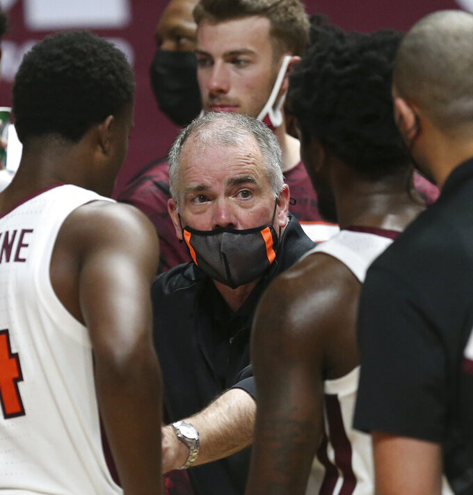 Virginia Tech head coach Mike Young speaks with his team during a timeout during the second half of an NCAA college basketball game against VMI, Thursday, Dec. 3, 2020 in Blacksburg, Va. (Matt Gentry/The Roanoke Times via AP, Pool)