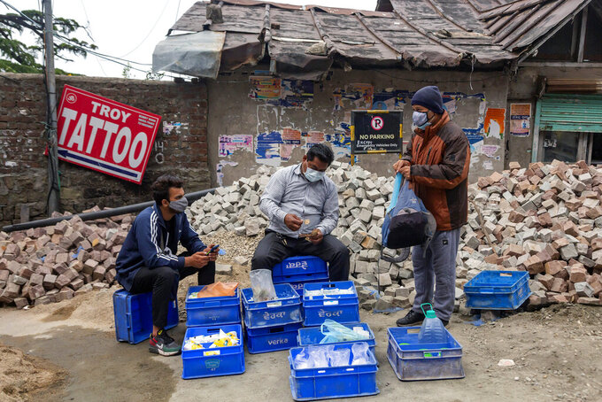 A vendor wearing a protective mask sells dairy products at the town square during a lockdown imposed to curb the spread of the coronavirus in Dharmsala, India, Saturday, May 29, 2021.  (AP Photo/Ashwini Bhatia)