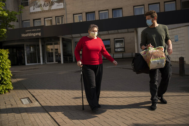 In this photo taken on Wednesday, April 29, 2020, Diane Wanten, 61, left, walks with her son Federico after being discharged from the Jessa Hospital in Hasselt, Belgium. Wanten was released from the hospital into home quarantine after being treated for two weeks in an ICU ward for COVID-19 coronavirus patients. (AP Photo/Francisco Seco)