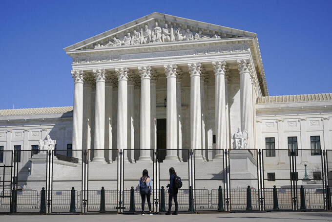 FILE - In this March 21, 2021, file photo people view the Supreme Court building from behind security fencing on Capitol Hill in Washington after portions of an outer perimeter of fencing were removed overnight to allow public access. A Supreme Court case being argued this week amid March Madness could erode the difference between elite college athletes and professional sports stars. (AP Photo/Patrick Semansky, File)