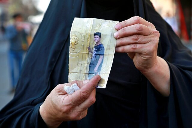 A woman holds a picture of her a missing son during anti-government protest in Baghdad, Iraq, Sunday, Feb. 23, 2020. There are 25 activists still missing since the protests erupted on Oct. 1, 2019, according to the semi-official Iraqi High Commission for Human Rights. No group has claimed responsibility but activists have blamed the militias. (AP Photo/Khalid Mohammed)