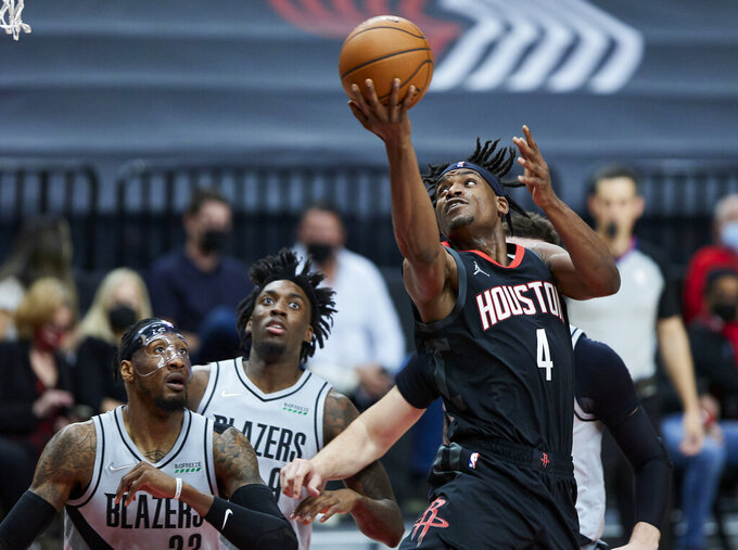 Houston Rockets forward Danuel House Jr., right, shoots over Portland Trail Blazers forwards Robert Covington, left, and Nassir Little during the first half of an NBA basketball game in Portland, Ore., Monday, May 10, 2021. (AP Photo/Craig Mitchelldyer)